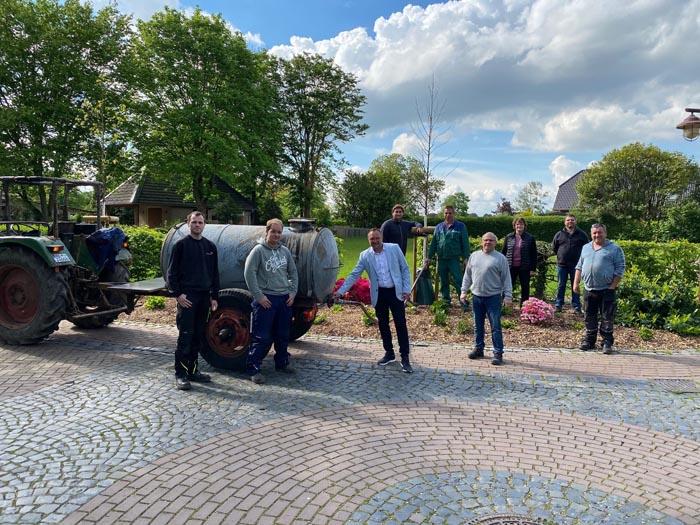 """""""Wasser marsch"""" für durstige Jungbäume, Bürgermeister Thomas Görtz (Bildmitte) dreht den Hahn auf und füllt gemeinsam mit Brudermeister Heinz Josef Bühren (5.v.r.) die Bewässerungssäcke."""